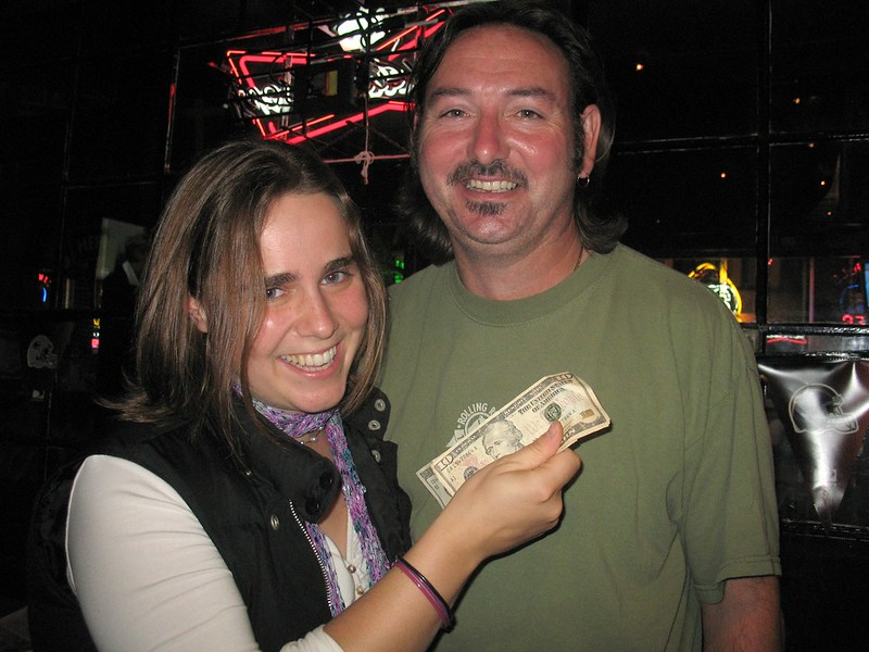 Woman holding prize money next to a man