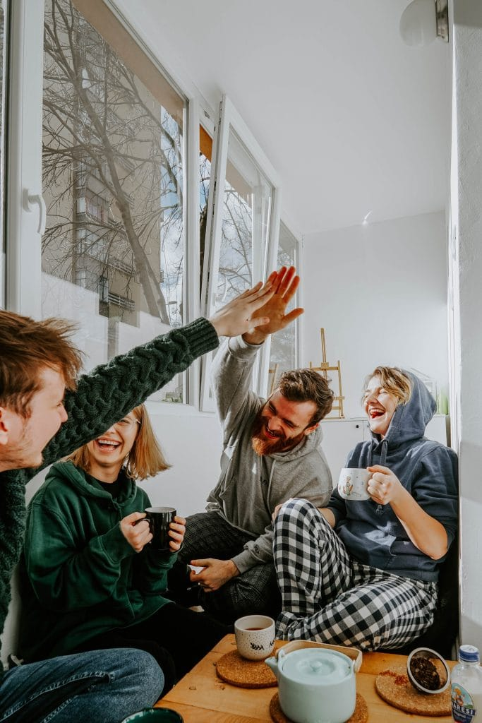 A group of friends sitting around high fiving