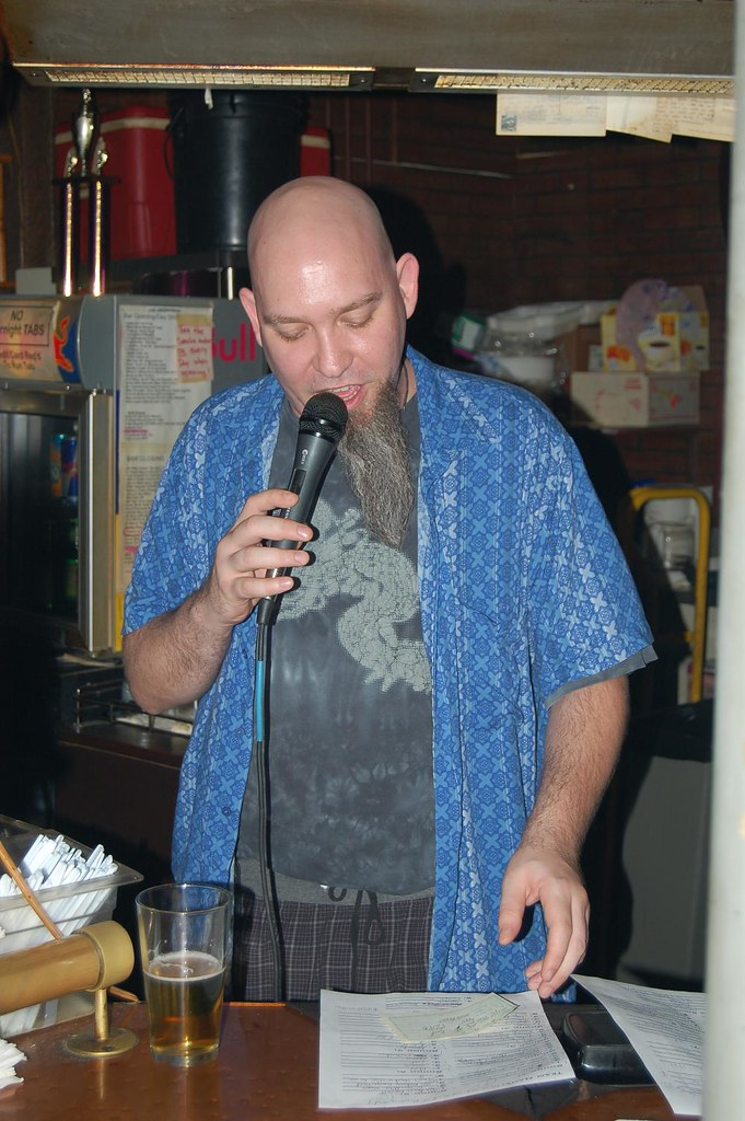 Trivia host with a mic, a beer, and a beard