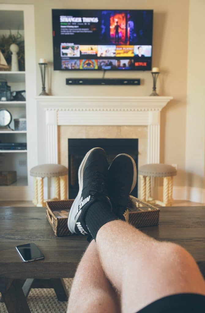 A guy's legs as he watches TV