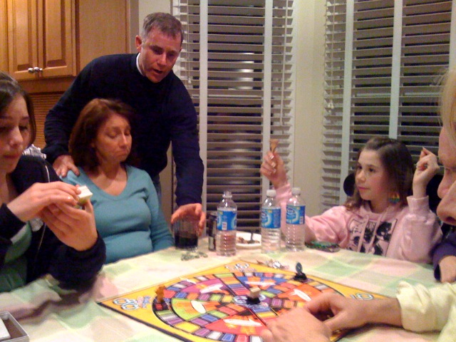 A family playing Trivial Pursuit