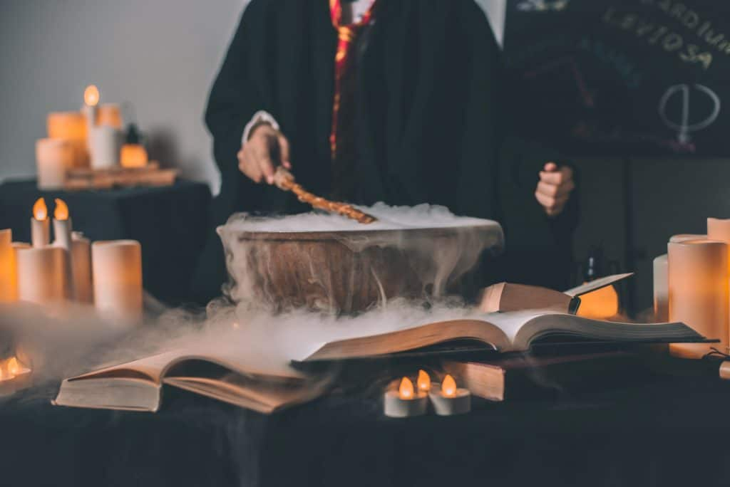 Harry Potter figure in robes with spellbooks and cauldron