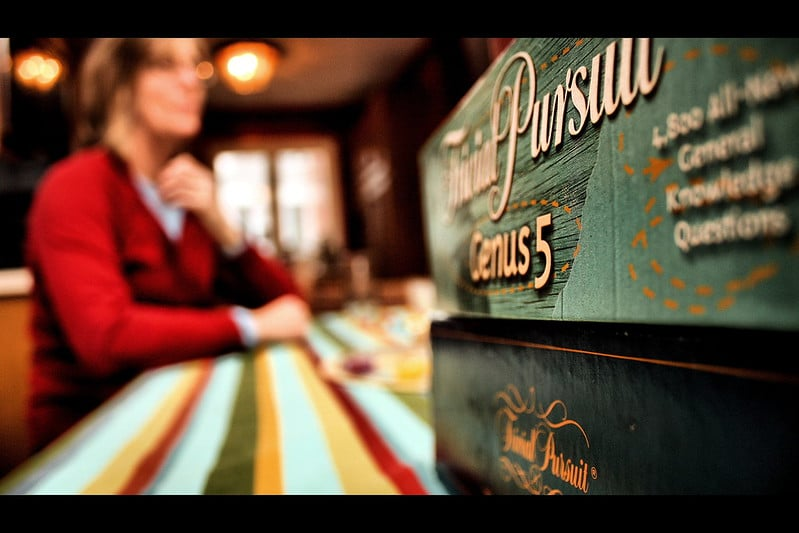 Woman sitting near a stack of Trivial Pursuit games
