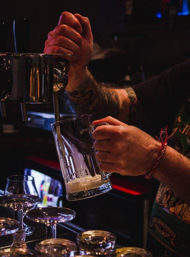 bartender pouring beer in a tap