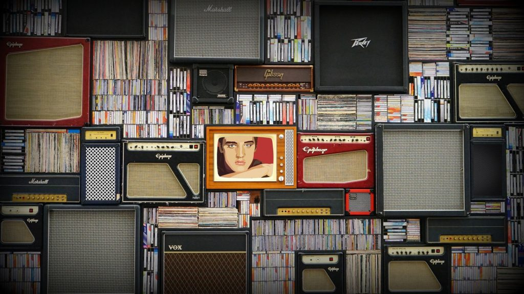 Stacks of records, CDs and speakers with a television featuring Elvis Presley's face in the middle.