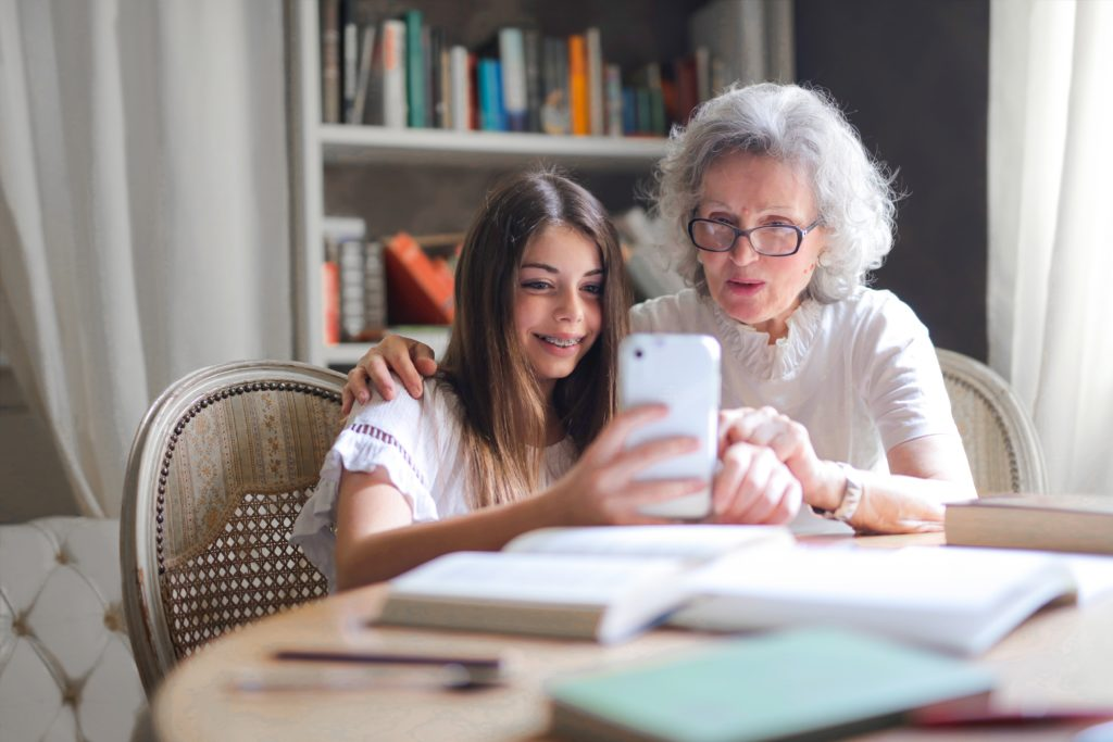 Grandmother and granddaughter take a selfie together.
