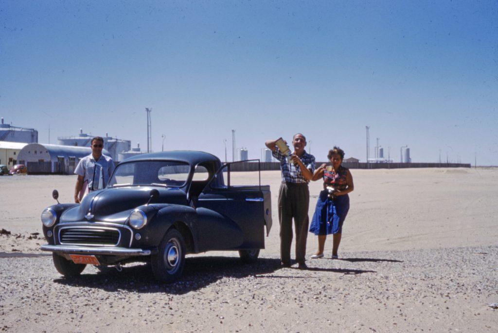 People on Beach Standing Beside Black Vintage Car in the 1960s