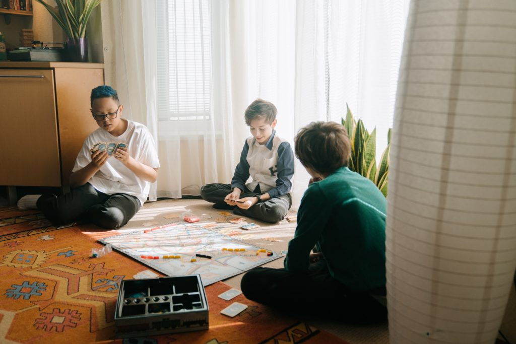 Three young boys playing a board game.