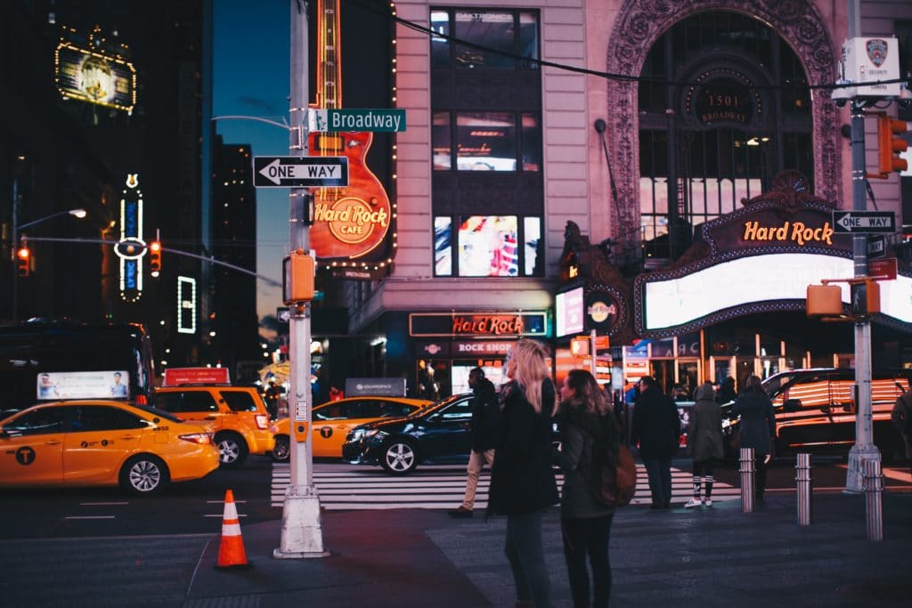 People standing near NYC Broadway at night.