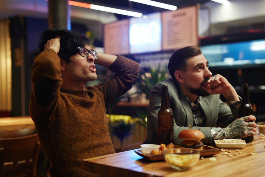 Two men watching a sports game at a bar.