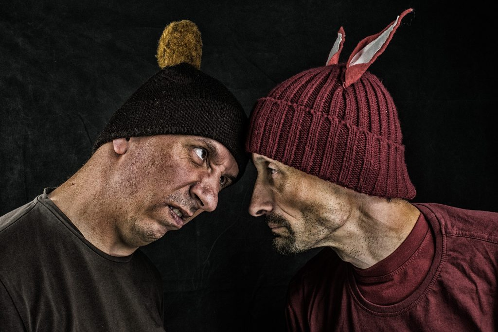 Two guys in winter caps have a staredown