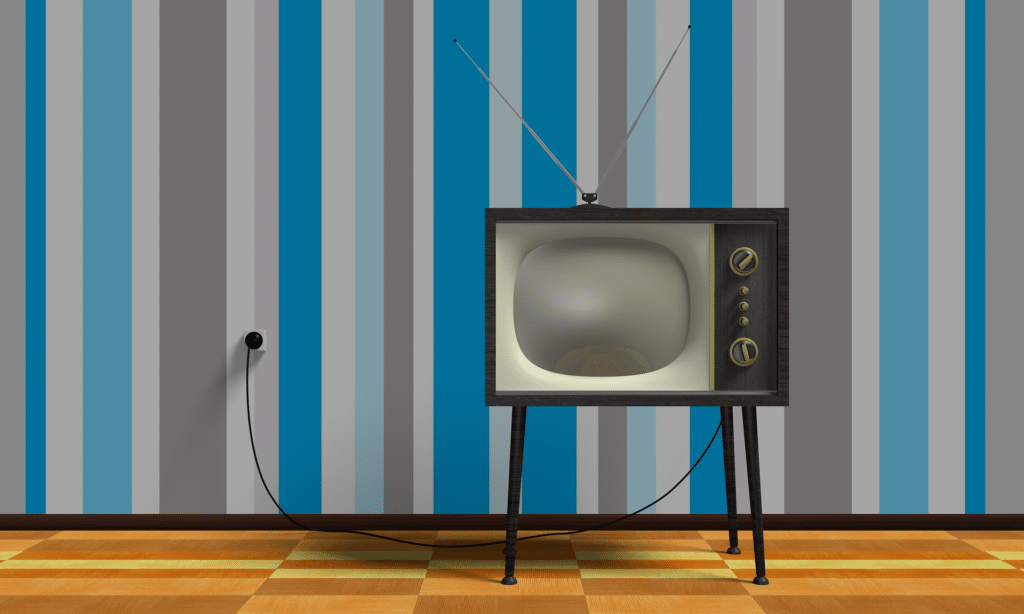 Retro television in front of a blue and grey striped wall.