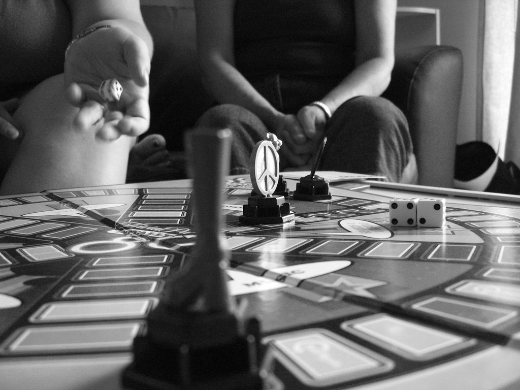 Black and white photo of two people playing Trivial Pursuit.