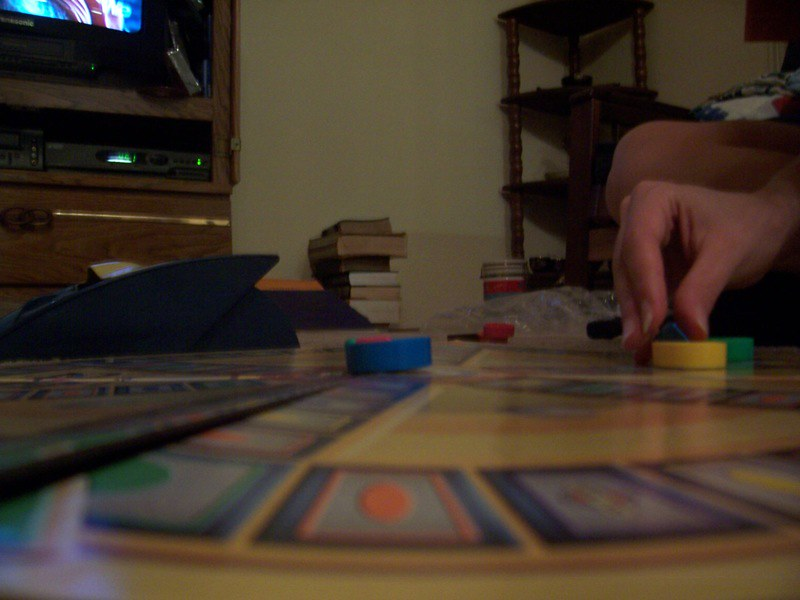Close up of someone's hand moving a Trivial Pursuit piece.