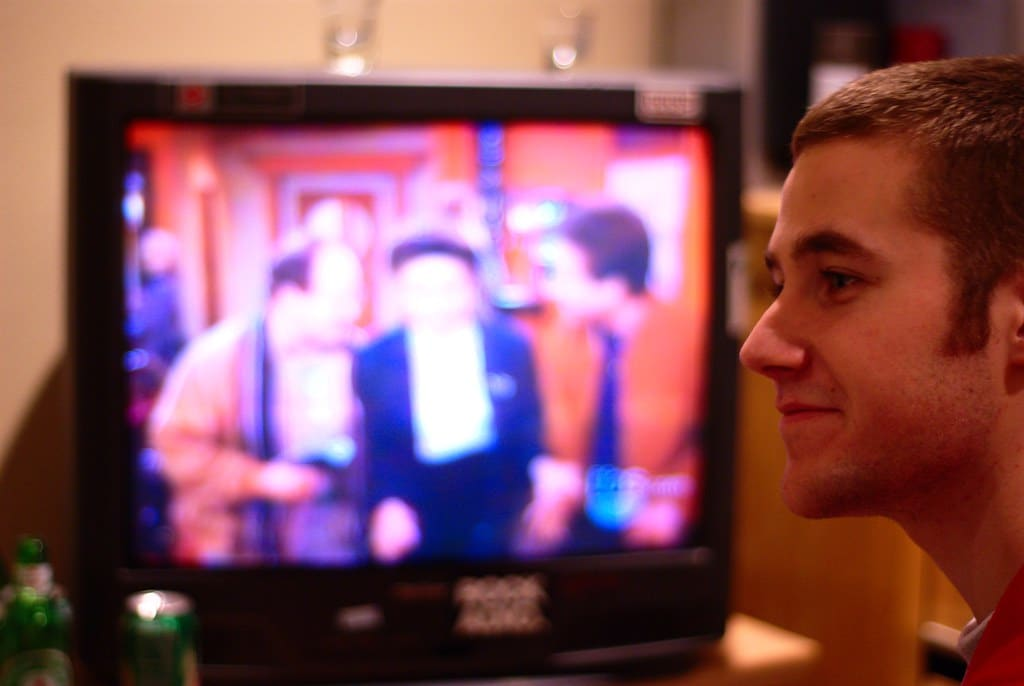 Close up of a man in front of a television playing Seinfeld.