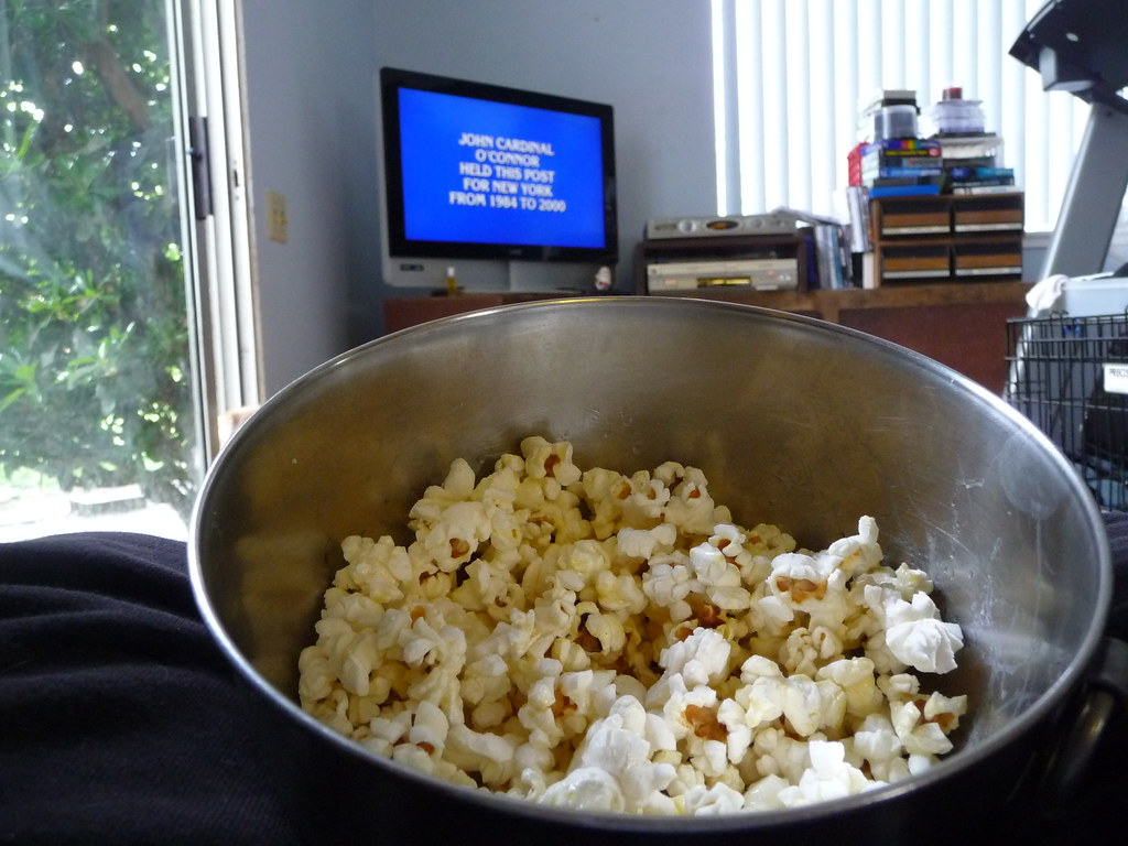 A bowl of popcorn in front of a TV airing Jeopardy!