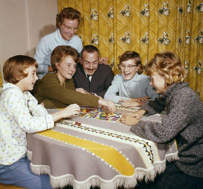 Vintage image of a family playing a board game.