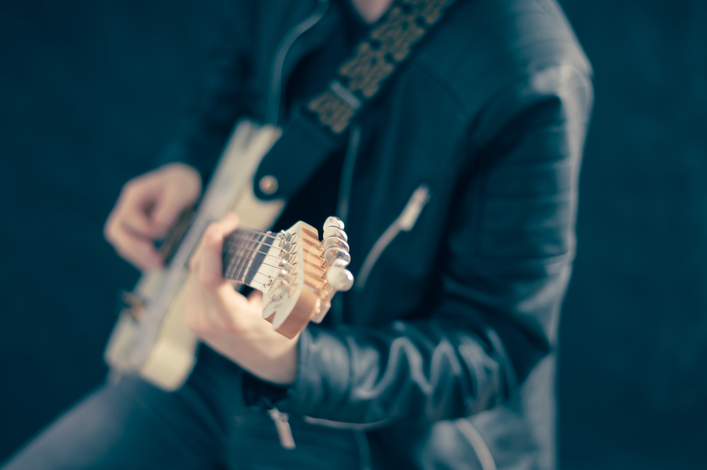 Close-up on a man in a leather jacket playing guitar.