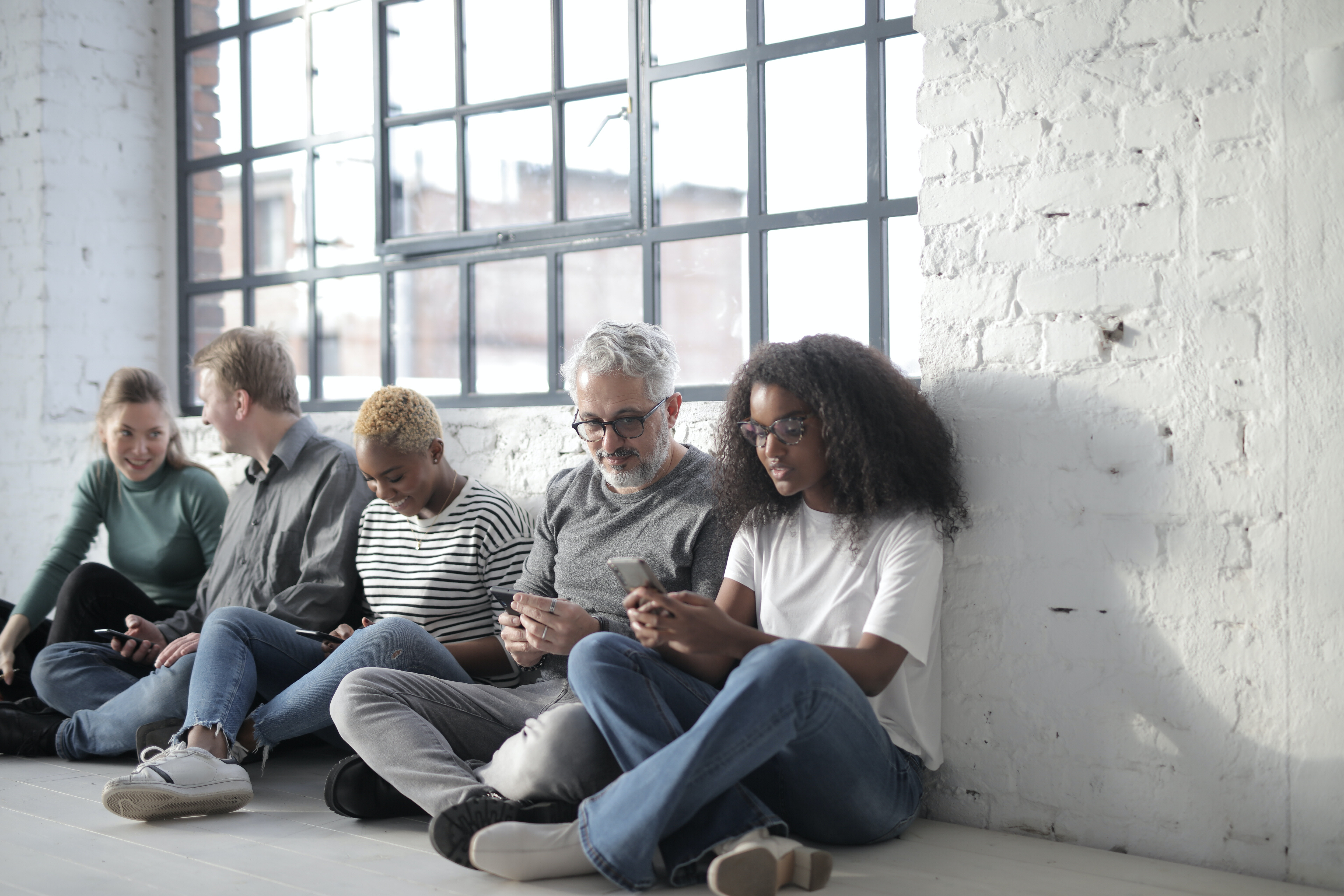 A group of men and women sitting in a hallway, looking at their phones.