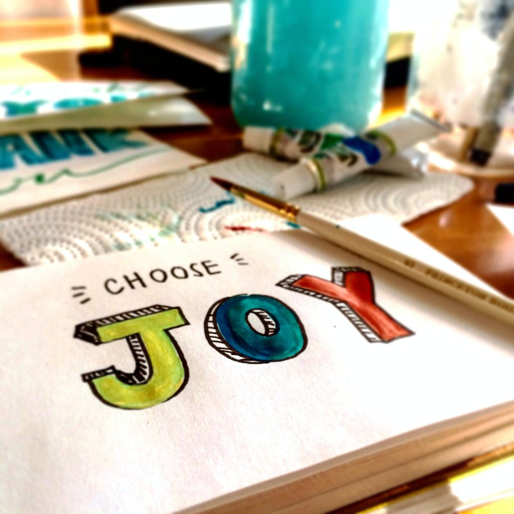 """White paper with the words """"Choose Joy"""" written on it."""