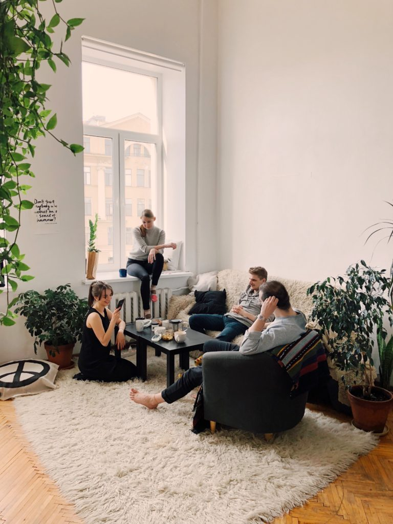 Two men and two women having a small indoor get-together.