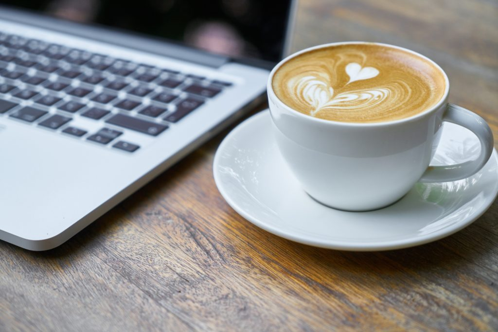 Cup of coffee on saucer next to laptop