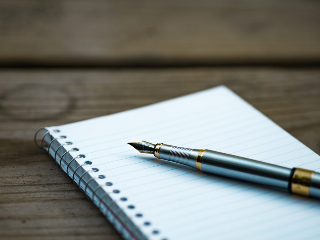 Closeup of a pen and a notebook.