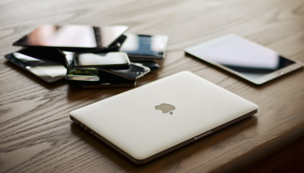 Macbook, Ipad, and other phones/ tablets on desk.