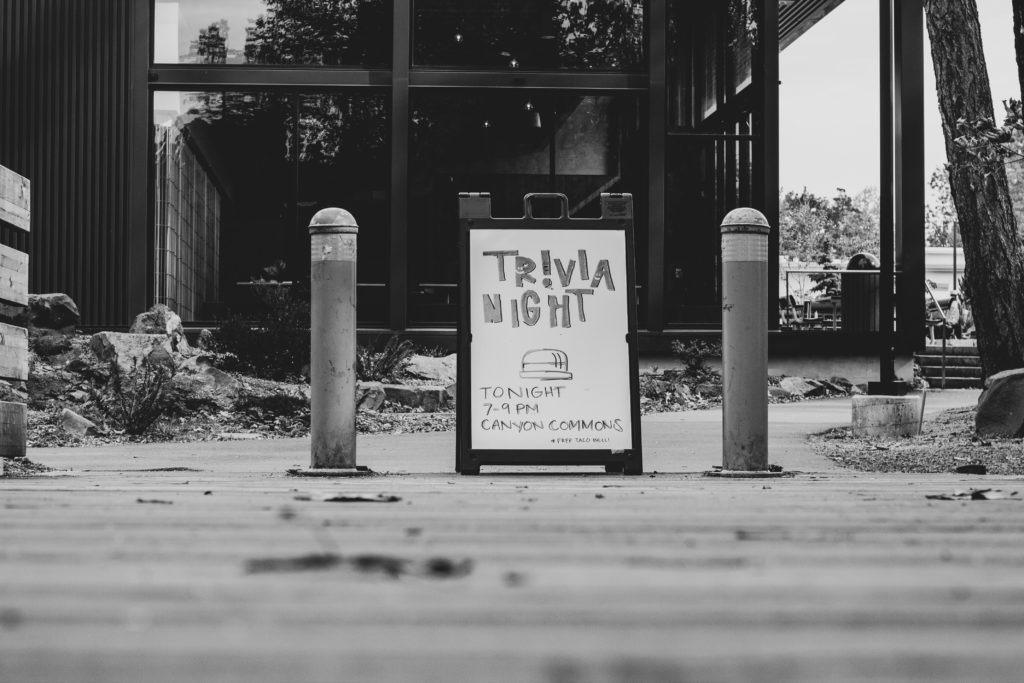 Black-and-white photo of a sign advertising a trivia night.