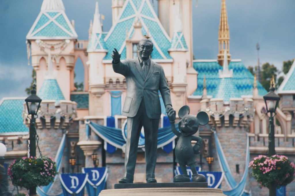 Statue of Walt Disney holding Mickey Mouse's hand in front of the Magic Kingdom in Disneyland, CA.