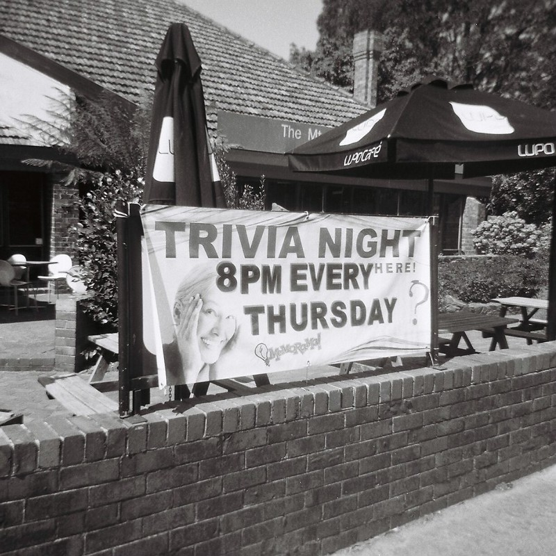 Black and white image of a sign advertising trivia night every Thursday at 8 PM