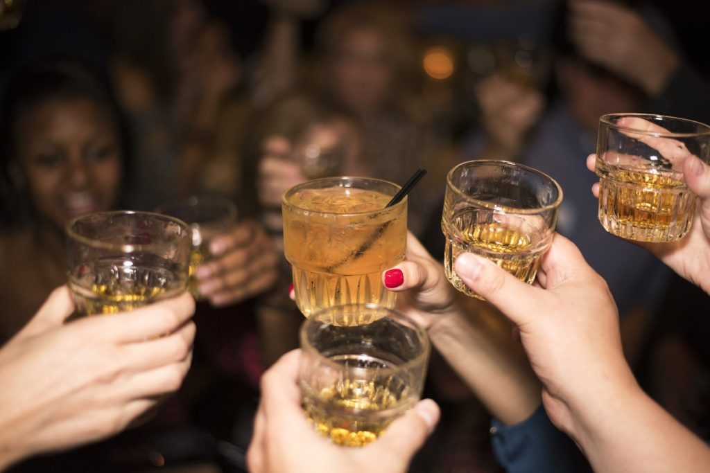 People raising a toast with glasses of whiskey.