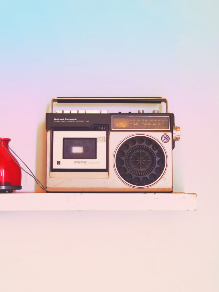 Photo of an old radio against a pastel-colored background.