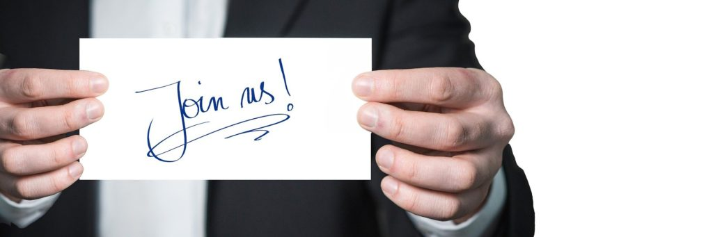 """Close-up of a man holding a white card that reads """"Join Us!"""""""