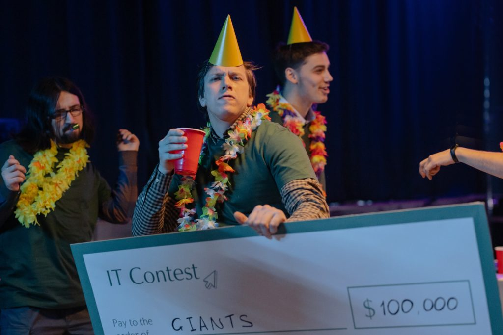 Guys celebrating with a giant check for $100,000.