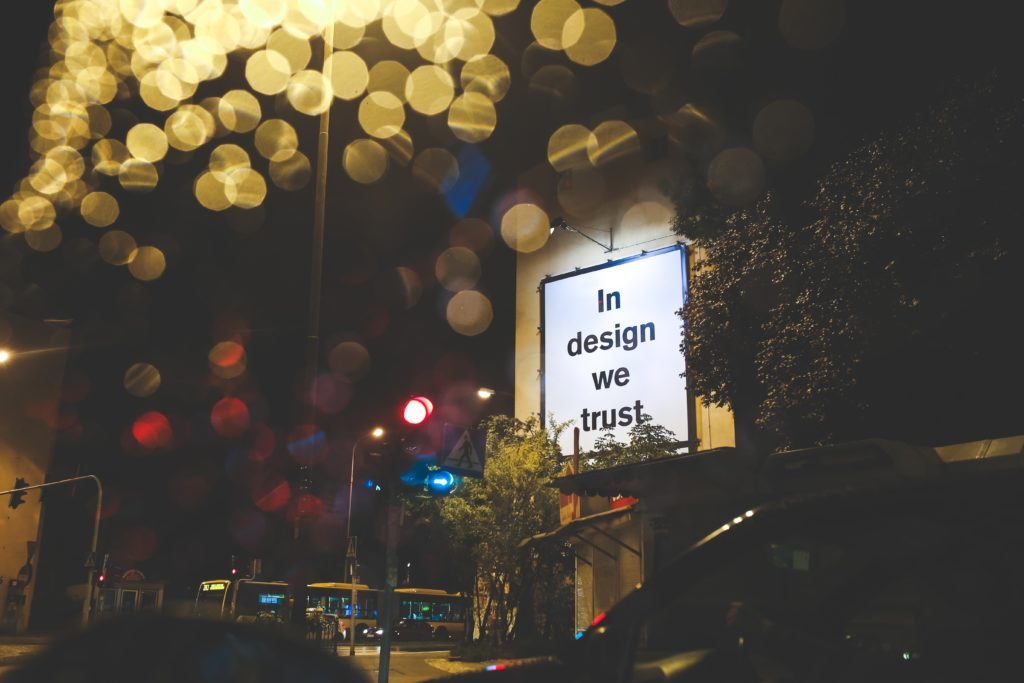 """A sign that reads """"In design we trust."""""""