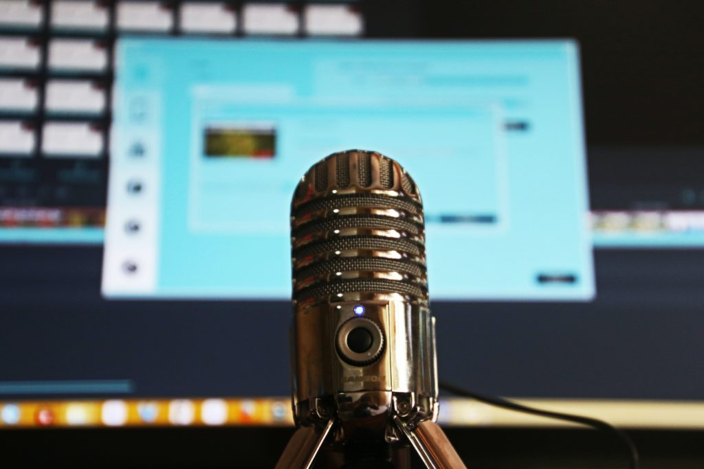 Microphone in front of a computer screen.