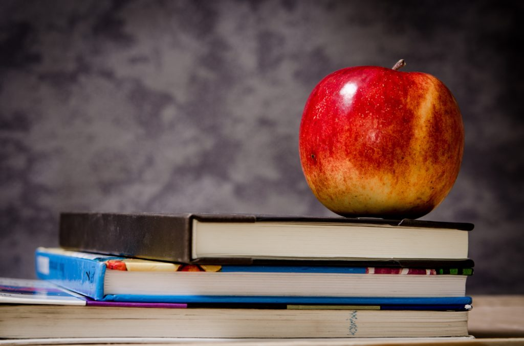 A stack of textbooks with an apple on top.