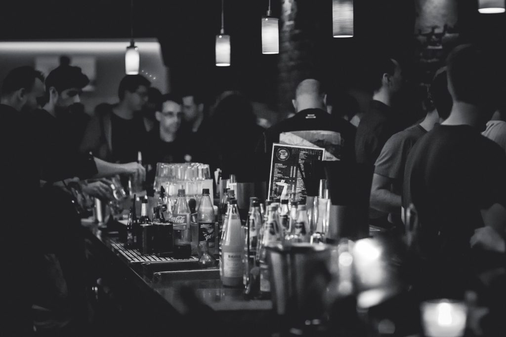 Greyscale image of people at a crowded bar.