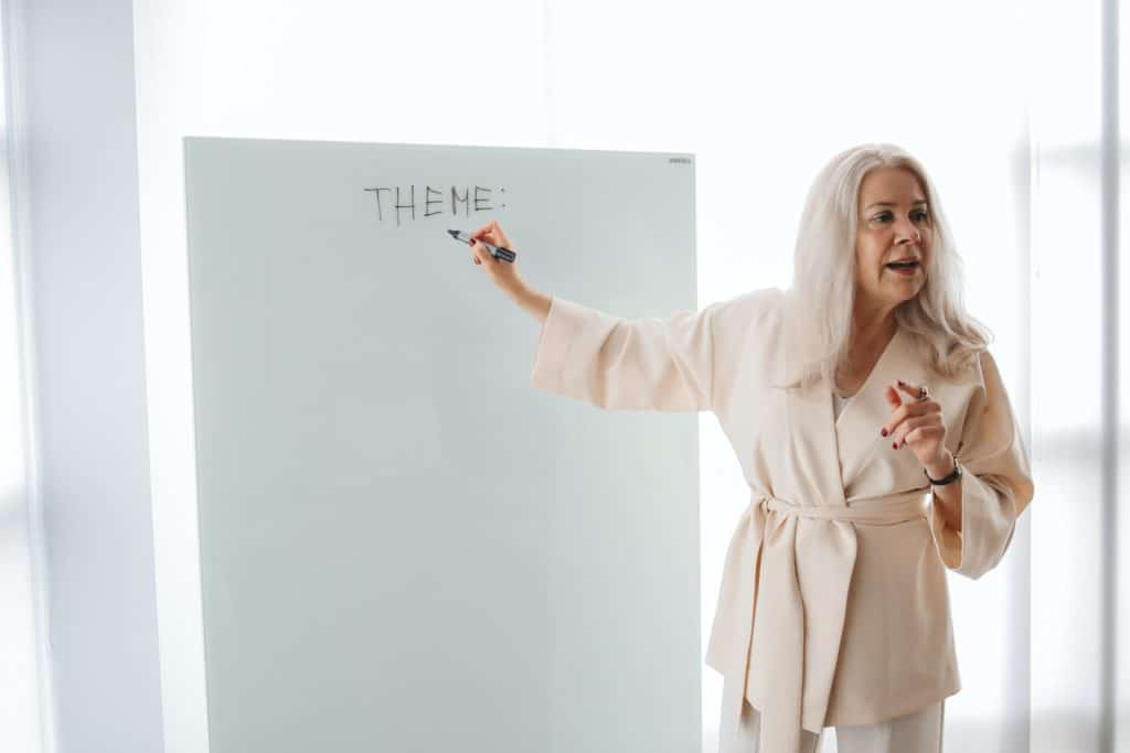"""White-haired woman writing the word """"theme"""" on a whiteboard."""