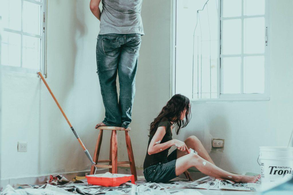 Man and woman painting walls.