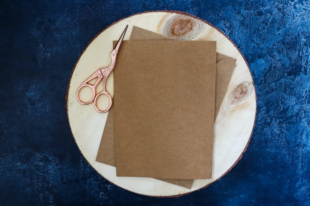 Brown cards and envelopes with copper scissors on a wooden stump against a blue background.
