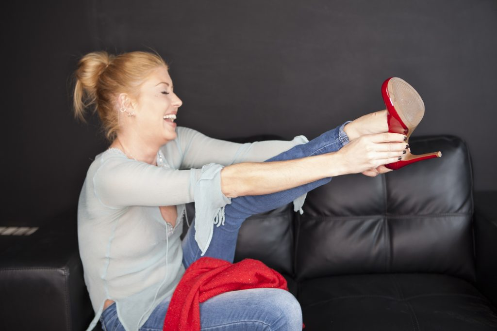 Blonde woman taking off a pair of red shoes.