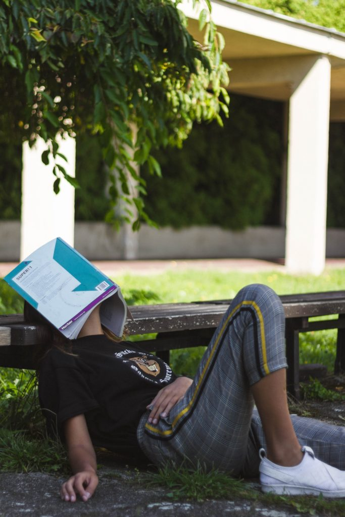 Girl sitting on grass with a book over her face.
