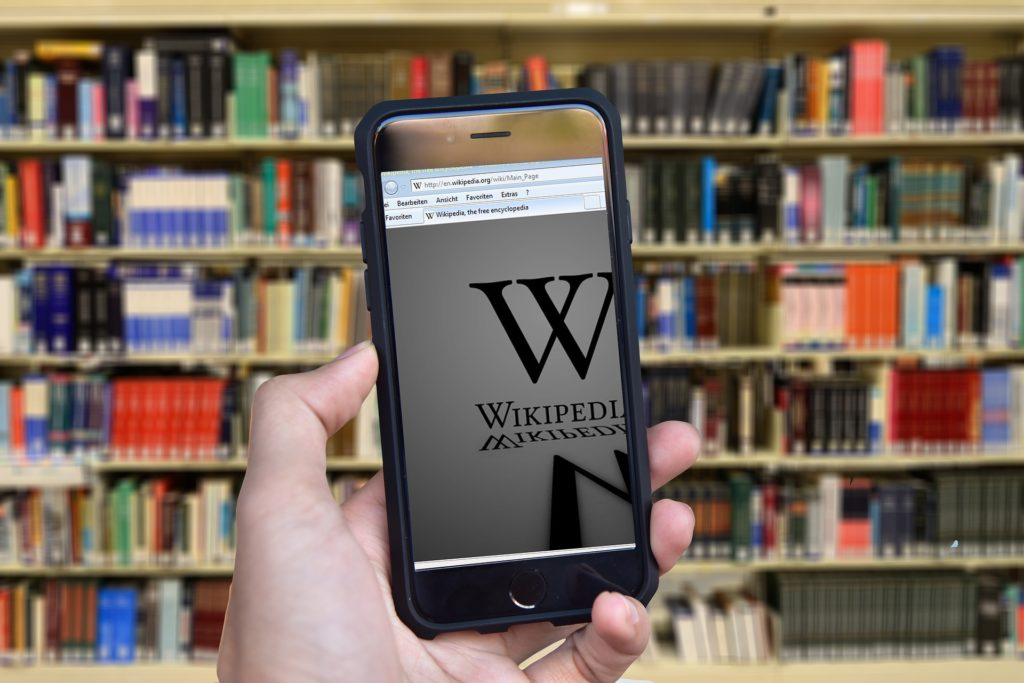 Smart phone displaying Wikipedia in front of shelves of books.