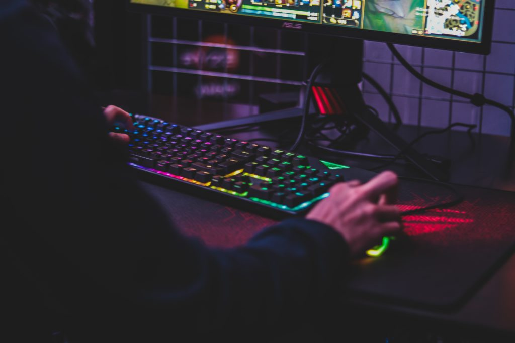 Person using a gaming computer with a headset and light-up keyboard.