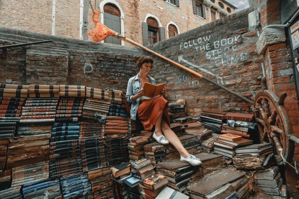 Woman reading on top of a large pile of books.