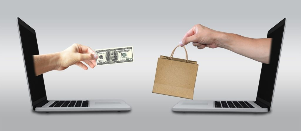 Two laptops facing another, exchanging money for a purchase.