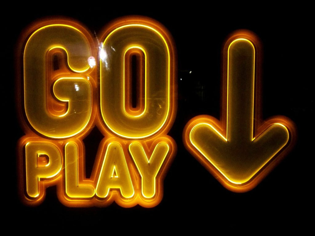 "Neon sign that reads ""GO PLAY"" with an arrow pointing down"