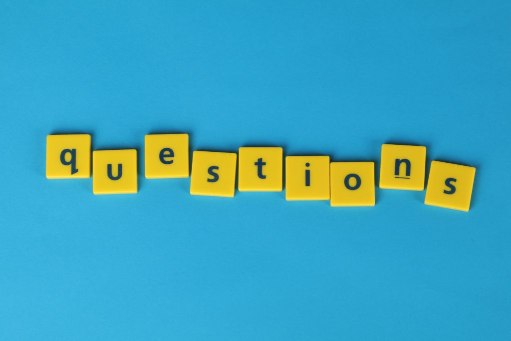 """Yellow squares spelling out the word """"questions"""" on a blue background."""